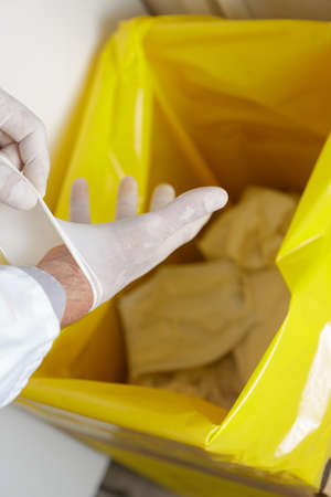 healthcare professional throwing away disposable latex gloves in trash