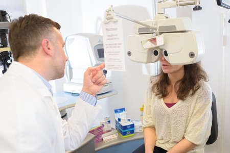 male optometrist doing sight testing for female patient