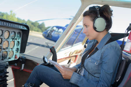 female helicopter pilot reading a manual while sitting in cockpit