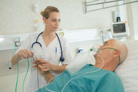 doctor assisting patient with oxygen mask in hospital room Stock Photo