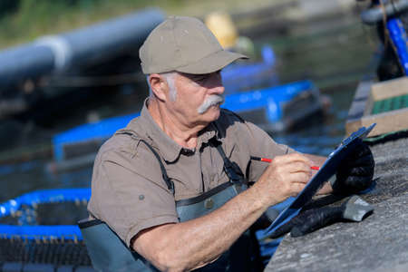coldblooded: man writing notes in his clipboard while working in fish-farm Stock Photo