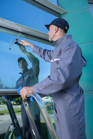 man cleaning windows with squeegee Stock Photo