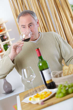gentleman holding a glass of wine and smelling the wine