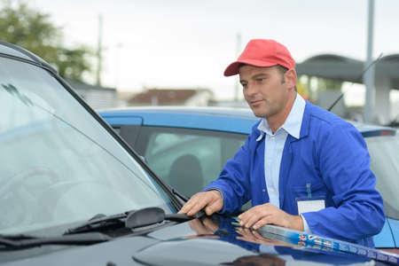 windscreen wiper replacement by professional auto service technician Stock Photo