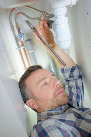 sink: plumber repairing a pipe under a sink