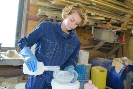 female worker making fiberglass to fix a boat in workshop