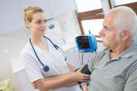A female doctor checking an old mans arterial blood pressure Reklamní fotografie