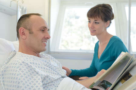 sick man in hospital reading Stock Photo