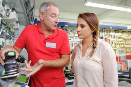 new addition: women assited while buying a tool in a hardware Stock Photo