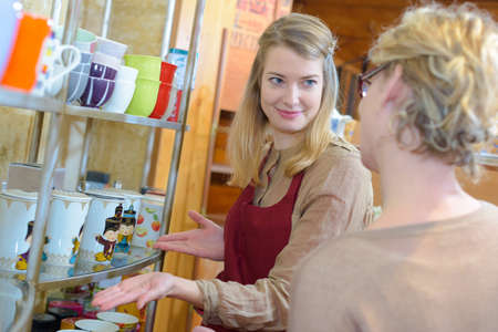 woman being assisted to choose cup in a shop Stock Photo