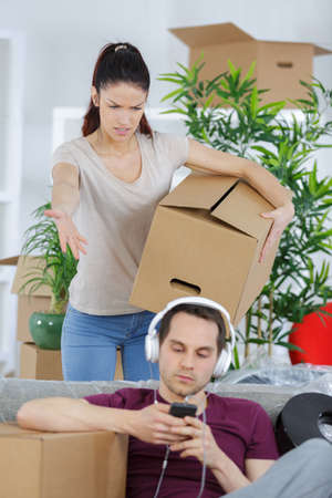 woman packing moving boxes and her lazy boyfriend Stock Photo