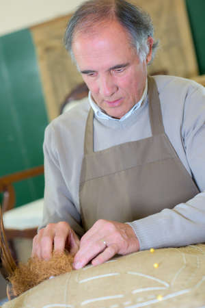 upholstered: craftman fixing a split seat on a chair