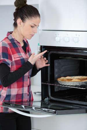 젊은 여자가 요리하는 동안 손을 태워