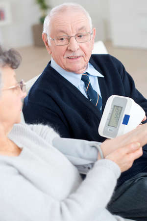 old couple helping eachother to measure blood pressure Stock Photo