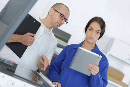 male and young female workers discussing with a tablet Stock Photo