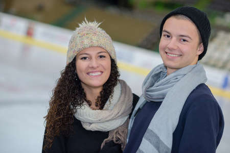 young couple standing in open ice rink