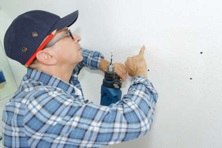 Senior man drilling holes in wall