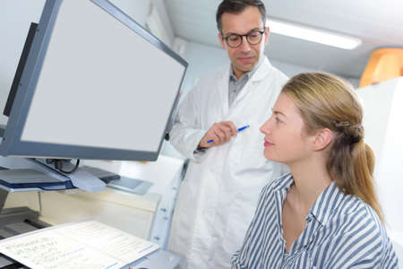 patient and doctor look at screen tp discuss treatment details Stock Photo