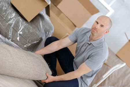 man unpacking sofa
