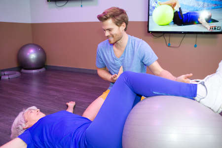 senior woman doing pilates with physical therapist