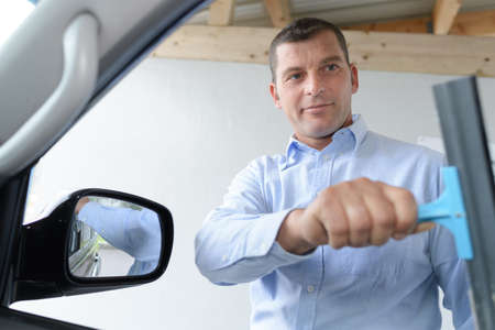 gloss: man cleaning car window with squeegee