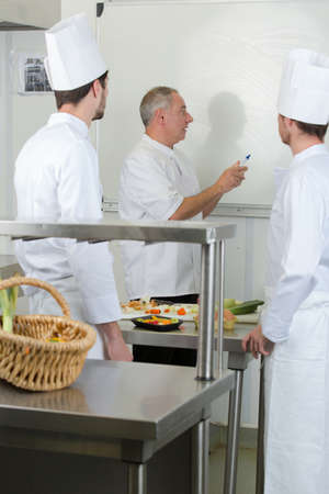 subsequently: chef writing recipe on a board for apprentices Stock Photo