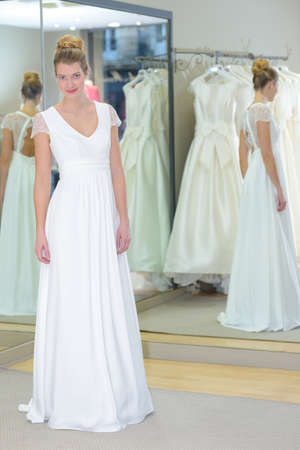 miror: girl standing in the bright studio in a wedding dress