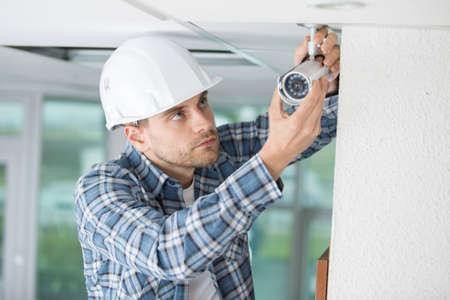 young male technician installing camera on wall