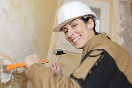 woman construction worker chipping away plaster Stock Photo