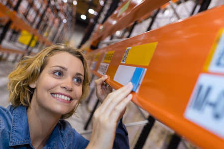 happy warehouse worker putting prices on shelves Stock Photo