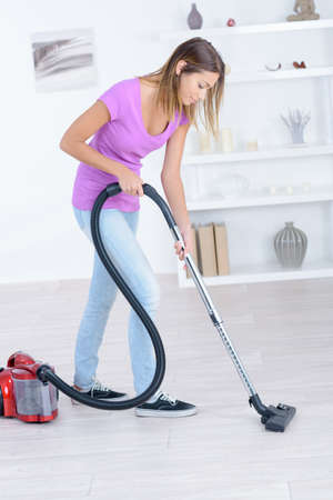 young woman cleaning floor with hoover