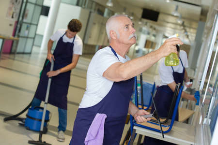cleaning team mopping floor windows