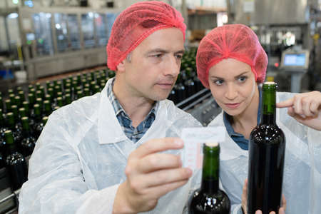 positive smiling expert woman with co-worker on wine factory