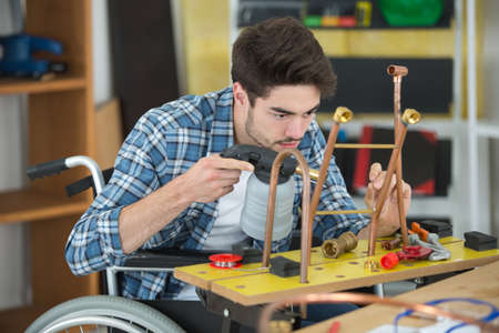 manual worker in wheelchair welding cooper pipes Stock Photo