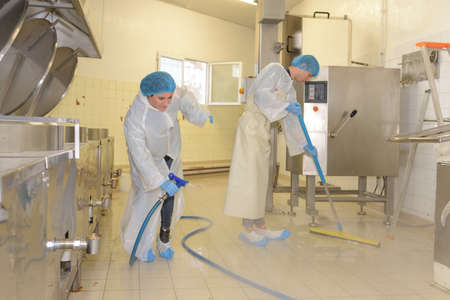 factory worker cleaning floor