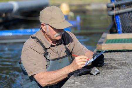 senior fish farm employee taking notes on clipboard