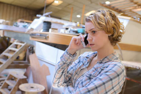 young woman on the phone in marine workshop Stock Photo