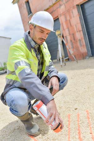 young surveyor spraying mark on floor Stock Photo - 85610543