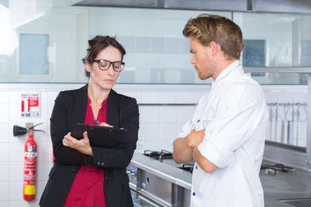 vrouwelijke inspecteur in restaurantkeuken met chef-kok