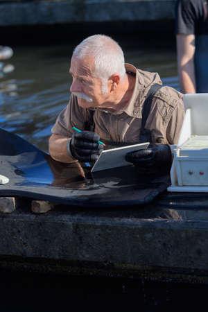 soon to be retired fish farm employee taking notes Stok Fotoğraf