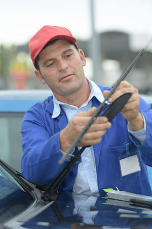man is changing windscreen wipers on a car Stock Photo