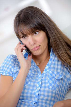 beautiful girl talking on the phone with displeasure Stock Photo