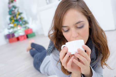 portrait of woman lying on the floor drinking coffee Stock Photo