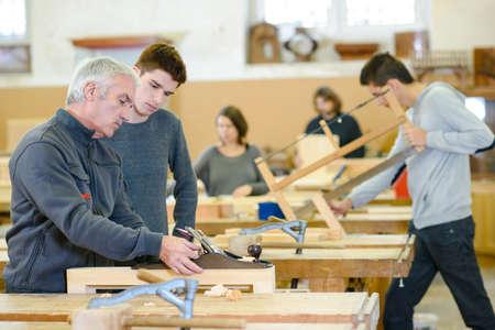 student and teacher in carpentry class Foto de archivo