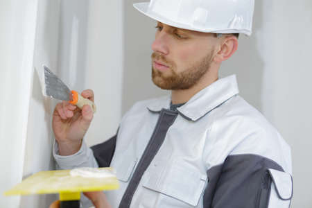 construction worker plasterer with trowel plastering a wall Stock Photo