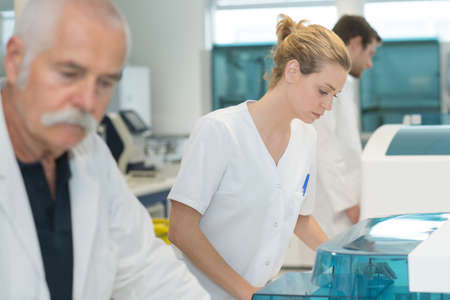 group of scientists studying new substances in flasks Stock Photo