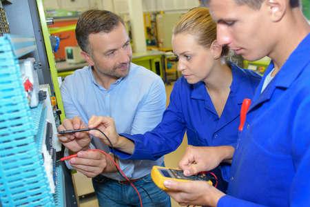 Lehrer, der die Schüler an elektrischen Schaltkreisen auswertet