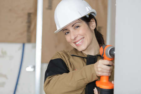 woman worker drilling something at construction site Stock Photo