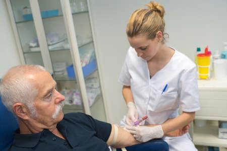 nurse giving injection to senior man Stock Photo