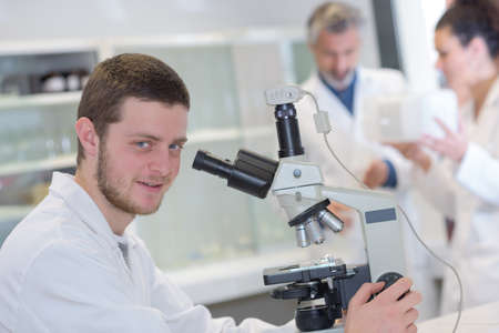 young male scientist with a microscope checking his sample